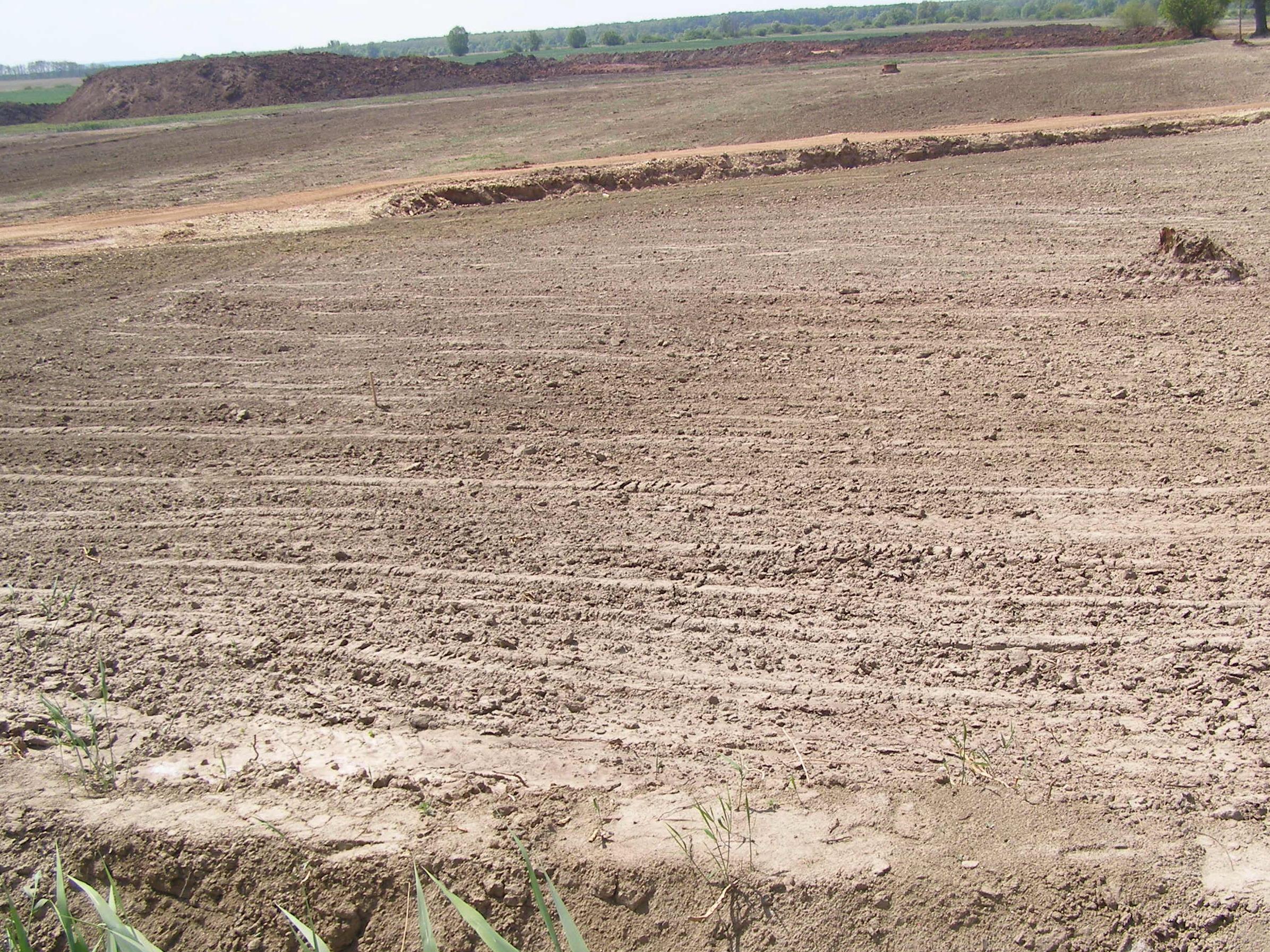 Letakarított szántóföld, háttérben a leszedett vörösiszap kupacok